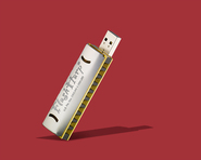 FlashHarp harmonica USB against red.